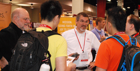 Bro. Dennis Schimtz, Bro. Tom Wendorf and Bro. Brandon Paluch (in background) talk to young visitors to the Marianist booth.