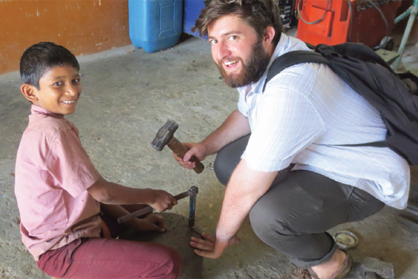 University of Dayton student Jake Scara lends a hand to a student at the Marianist Skills Training Center in Deepahalli, India.