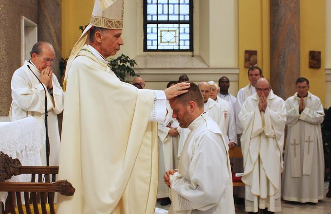 "In Rome, Archbishop Luis Francisco Ladaria Ferrar performs the ""imposition of hands"" in the rite of diaconate ordination of Bro. Bob Jones."