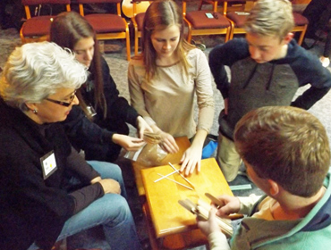 Pati Krasensky, left, works with retreatants in an exercise on cooperation and resource allocation.