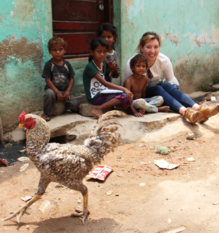 In the slums of Bangalore, St. Mary's University student Gisell Orozco reads a book to children sitting on the streets .
