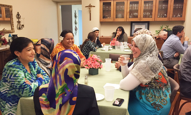 At left, Jenee Gonzalez, a member of the Marianist development office, and Makena Hamilton, activities coordinator at the Marianist Residence Community, converse with Turkish-American women before the Iftar dinner.