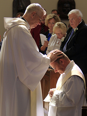 As part of the Rite or Ordination, Fr. Bill Meyer imposes hands on Fr. Sean.
