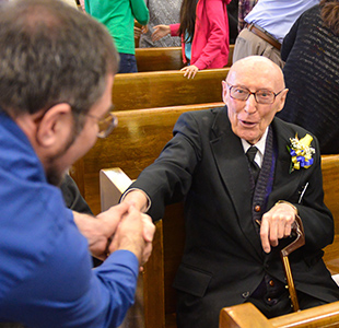 Bro. William Chewing, a 75 year Marianist is greeted during the Marianist Heritage Mass at St. Mary's University in San Antonio.