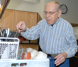 Loading the diswasher is among Bro. Francis' regular chores at his St. Louis community.