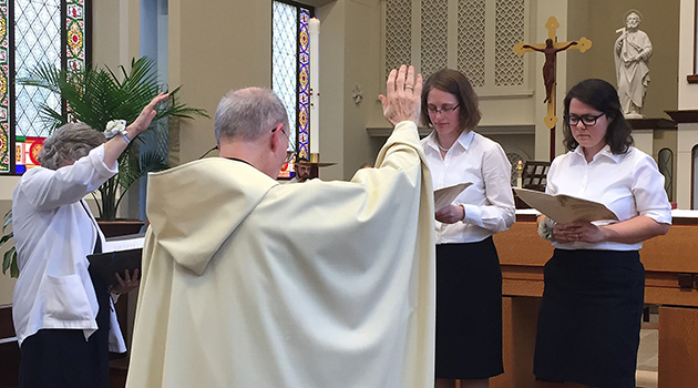 Sr. Laura Leming and Fr. Jim Schimelpfening lead a blessing of newly-vowed Srs. Caitlin and Gabrielle.