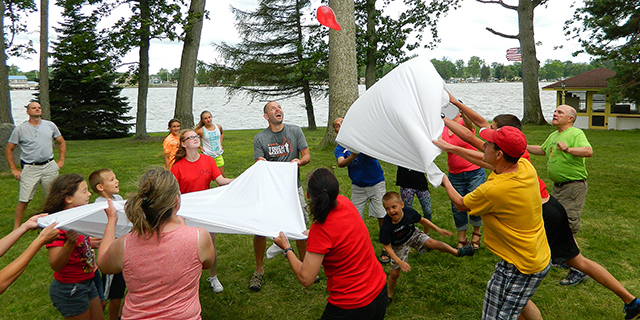 "Participants at the Family Retreat at Governor's Island Community in Ohio join in a lively balloon toss event during the ""family olympics."""